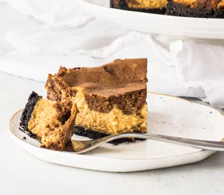 slice of chocolate pumpkin cheesecake on a plate with a fork taking a bite out of it