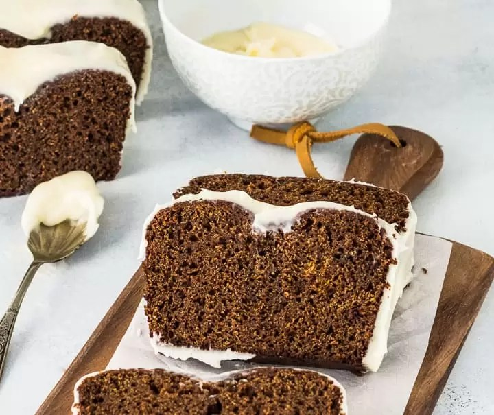 sliced gingerbread loaf on a wooden cutting board with a bowl of glaze behind it