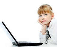 Shot of a little girl lying on a floor with her laptop. Isolated over white background.