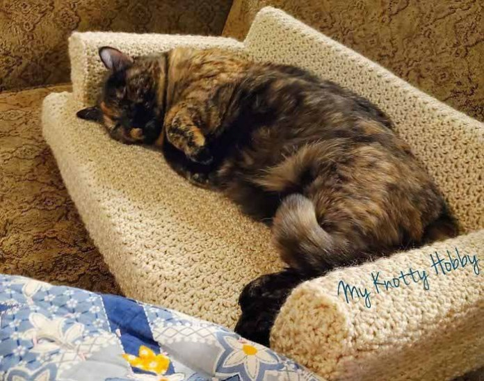 a tortie girl lays on a cream colored crochet cat couch