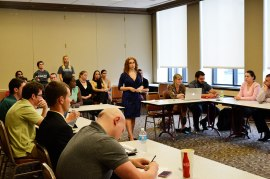 Criminal Justice Club President Christina Smith addresses the SGA with club members and advisers supporting her in the back.