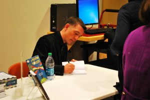 Author Joseph Bates signs his book for a student. (Photo/Nick Wort)