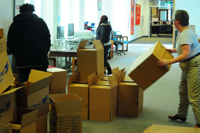 Business as usual continues in the Administration Building as boxes pile up around workers getting ready for a move. Photo Credit/Michael Montana