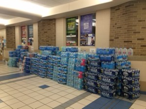 Cases of bottled water line the hallways of John Adams High School. Photo Credit/Gabriela Gil