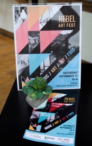The flyer for Rebel Art Fest sits displayed at MAKE South Bend along with an example of a DIY that will be available at the festival. PHOTO/Leah Fick