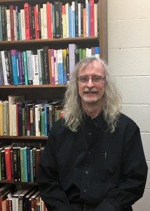 Associate Professor of Communication Arts Larry Lamber poses in front of one of his favorite things—books. PHOTO/Ashley Foor