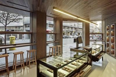 Vista al exterior con barras de degustación en diseño interior de Panadería Carnoedo