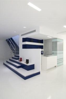 Diseño de óptica en Ponferrada. Detalle de la escalera y desembarco en forma de expositor, mostrador de atención y entrada a gabinetes