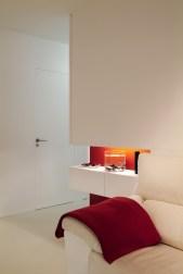 Diseño interior de piso en Galicia. Espacio decorativo y puerta baño al fondo. Interesante la forma de integrar las puertas, sin guarnición y totalmente enrasadas con el paño del pasillo