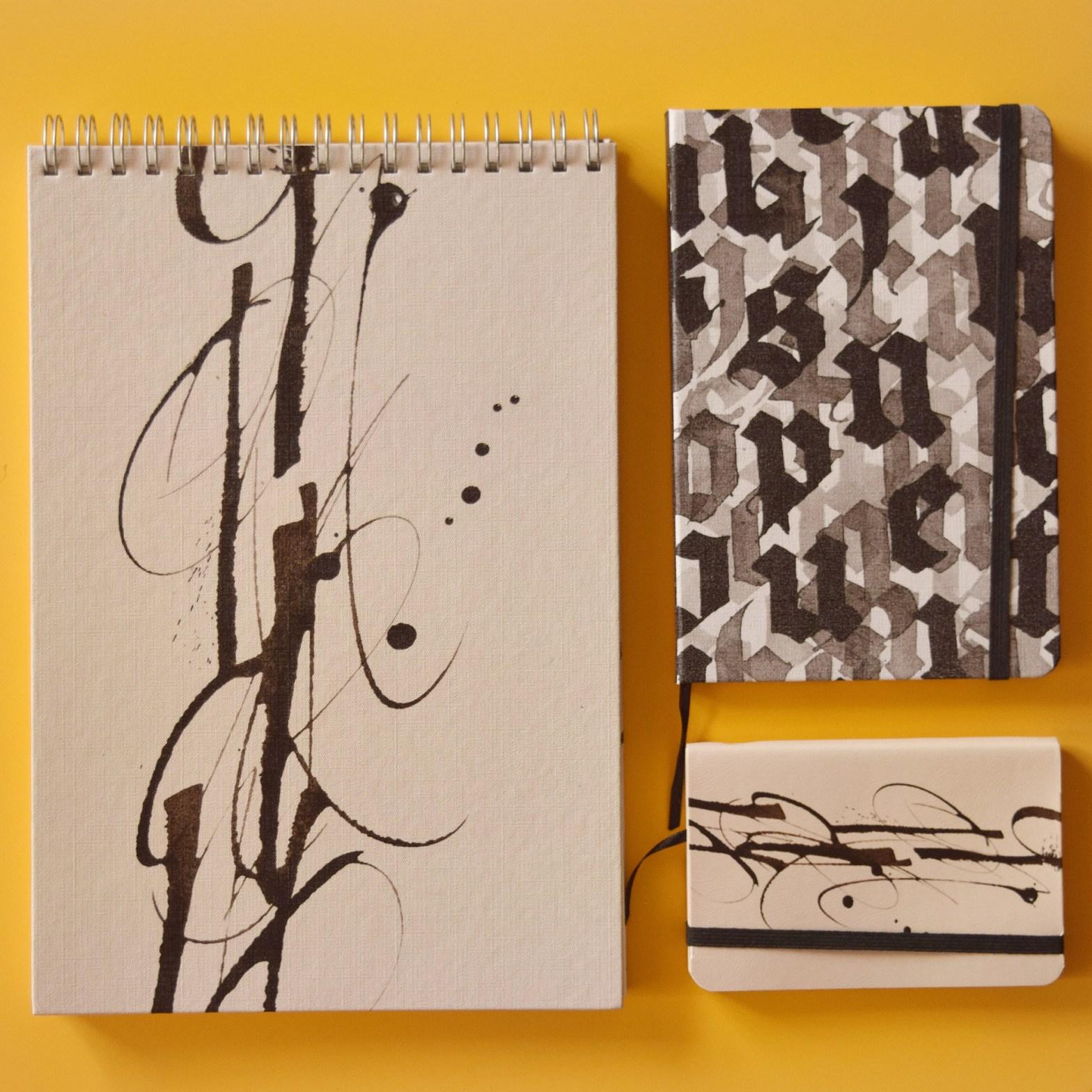 Os três modelos de cadernos da Taccbook assinados por Ivan Jerônimo, sobre fundo amarelo