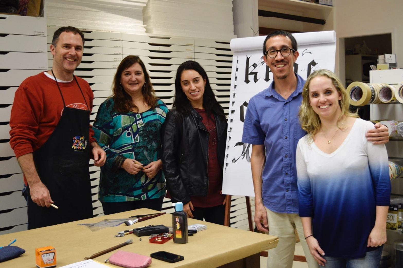Foto com quatro participantes da oficina e o instrutor, junto à mesa e à frente de um flowchart com modelos de letras