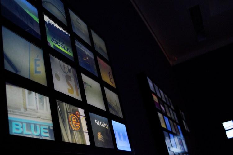 Ambiente com telas exibindo fotos de letras em placas e sinais urbanos