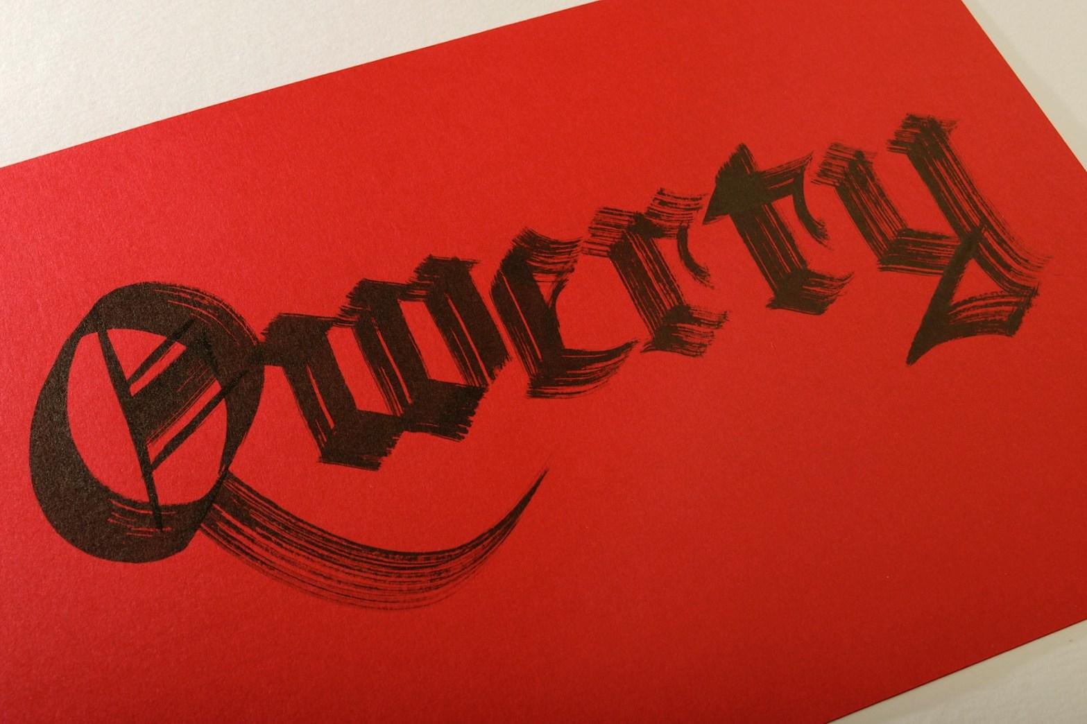 """Trabalho de caligrafia em preto sobre papel vermelho, onde está escrito """"Qwerty"""" em letras góticas"""