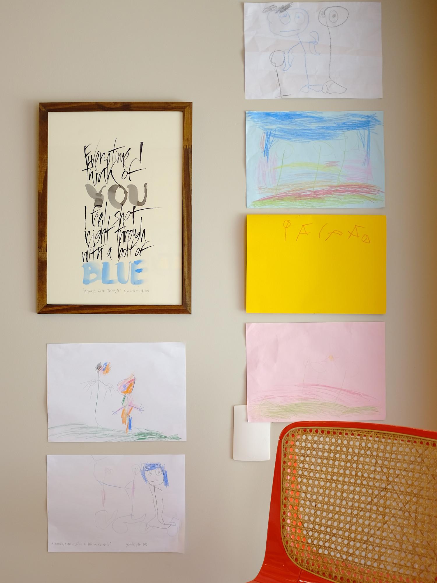 Obra de caligrafia na parede ao lado de desenhos de criança