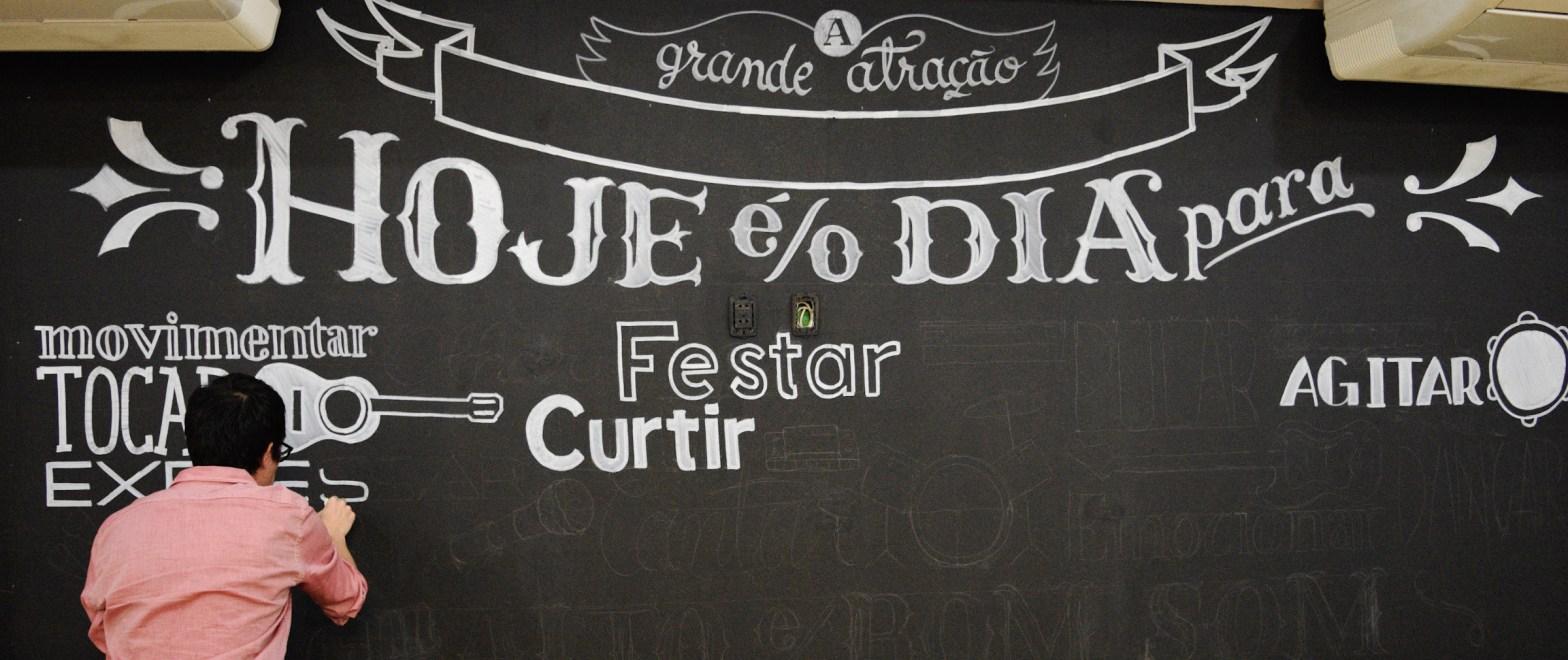 Autor trabalha em painel em lettering numa parede pintada de preto