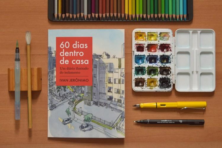 """Livro """"60 dias dentro de casa"""" sob uma superfície de madeira com canetas, lápis de cor e conjunto de aquarela"""
