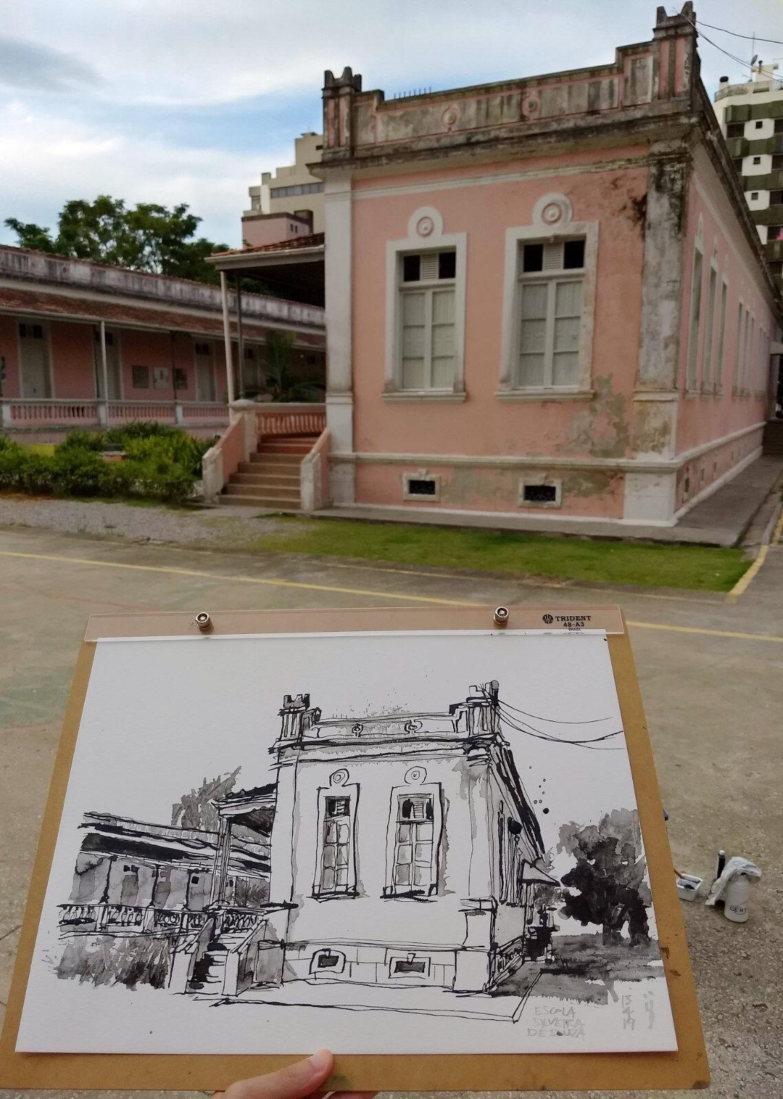 Fotografia da fachada traseira da escola, pintada em rosa claro, com o desenho em primeiro plano