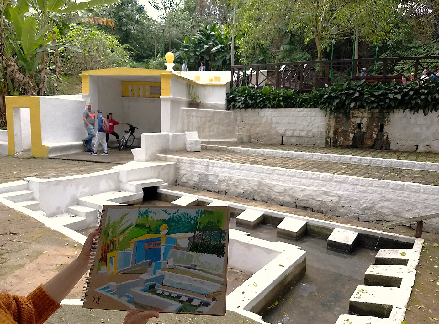 Ao fundo, estrutura da bica da carioca composta de tanque com blocos para as lavadeiras e uma pequena construção coberta. Em primeiro plano, sketchbook com o desenho