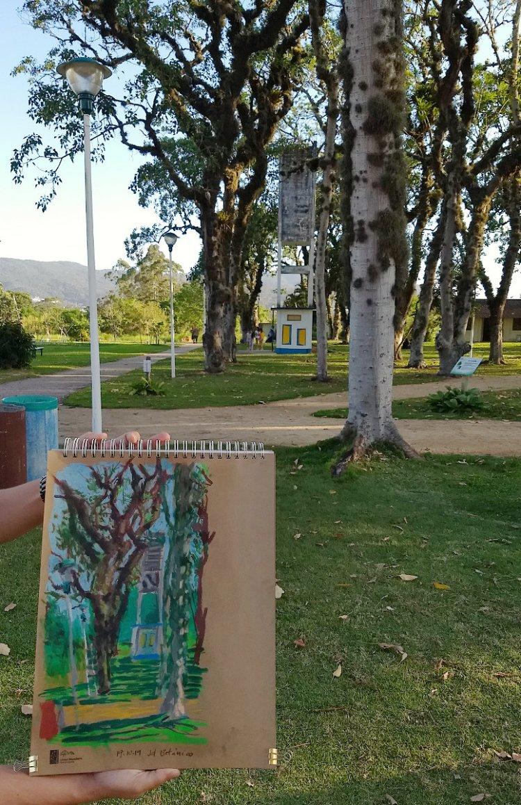 Cena do Jardim Botânico de Florianópolis em um dia ensolarado com árvores e uma caixa d'água ao fundo. Em primeiro plano, mãos seguram caderno com pintura me pastel seco