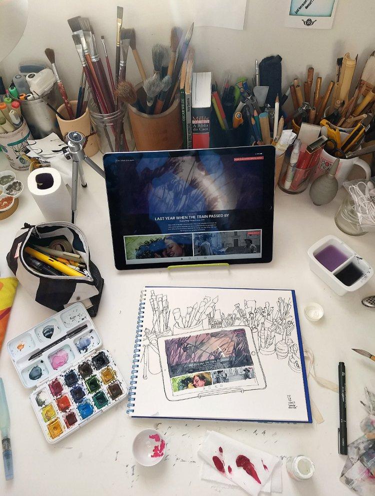 Mesa de desenho com o caderno, um tablet inclinado e vários materiais de desenho e pintura
