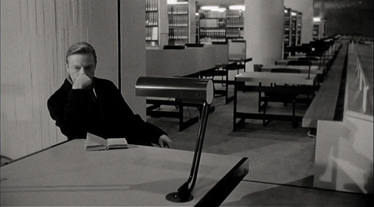 Cena do filme em que o personagem está na sentado em uma mesa na biblioteca com outras mesas e prateleiras ao fundo