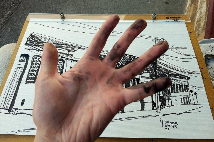 Mãos do autor manchadas de nanquim. Ao fundo, o desenho, já pronto