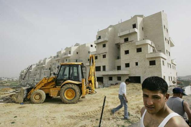Arabs working to build homes for Jewish settlers.