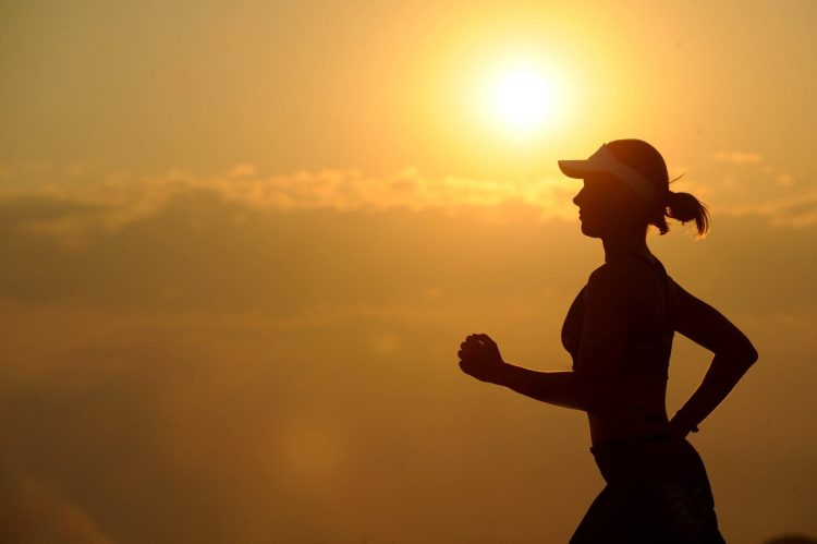 Silhouette of woman running past the sun.
