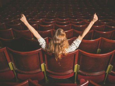 Rear view shot of an excited young woman sitting alone in an auditorium with her arms raised