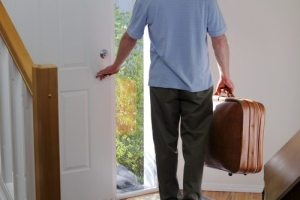 A man carrying a suitcase about to walk out the front door of his house to travel.