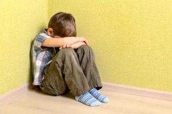 Little child boy wall corner punishment sitting