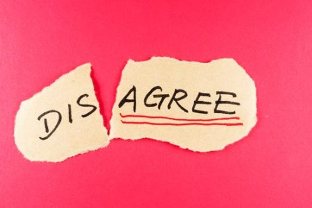 Disagree to agree concept words written on the paper against red background