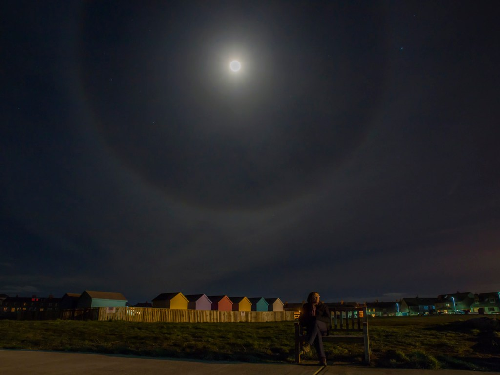 Nighttime shot of a moon halo with colouration, making it a moobow, in the sky above beach huts and my lovely wife sitting on a bench