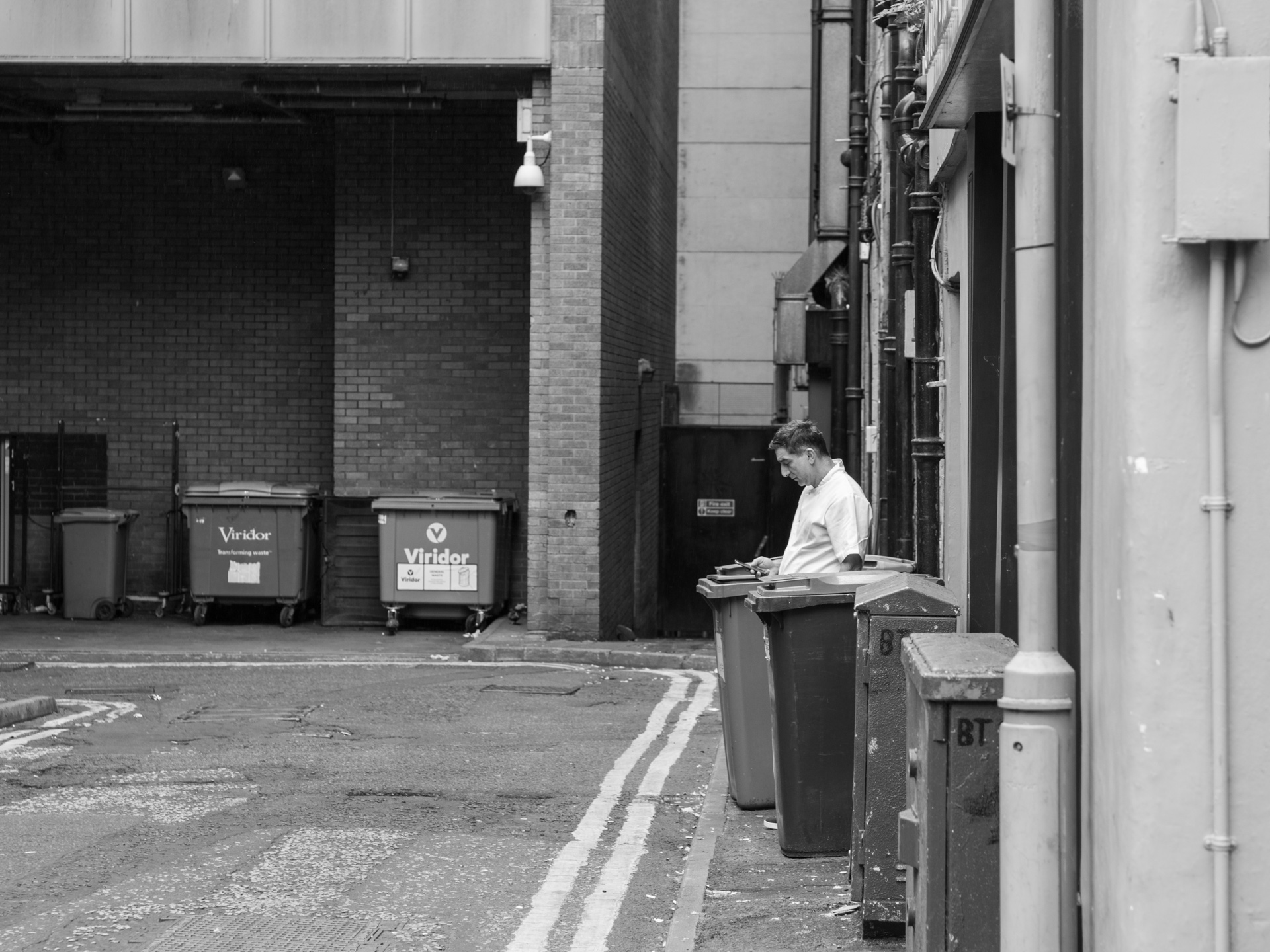 An employee steps out from the back of a kitchen for a break.