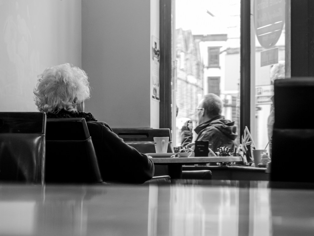 Person sitting at a table watching the the world go by, representing being stuck in a rut.
