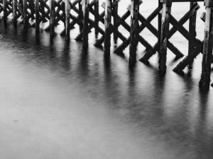 The legs of the pier in monochrome