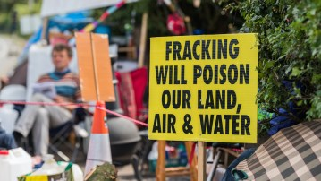 Photo of an anti-fracking protest sign with a man seated in the background