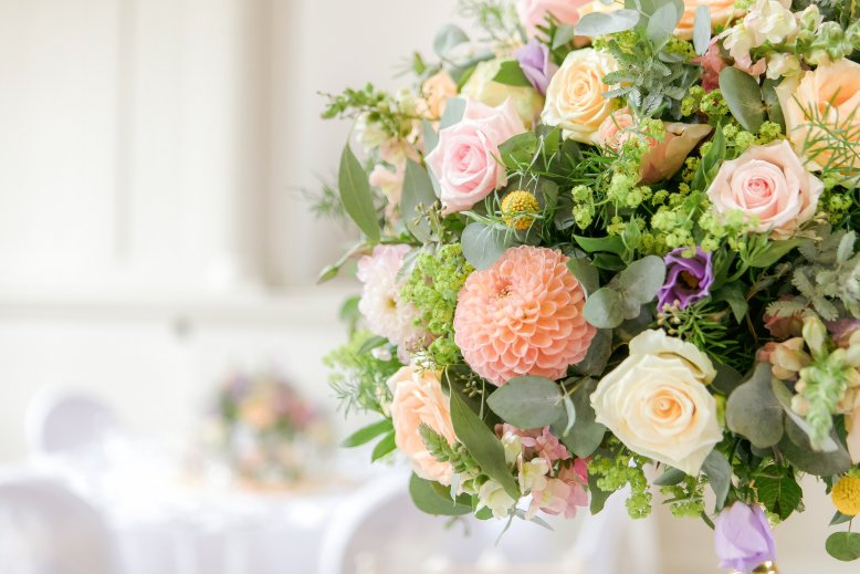 Close up of table arrangement in sorbet coloured flowers