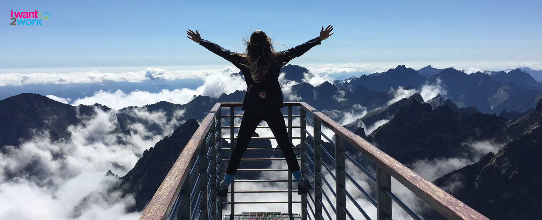 i want 2 work stand out from the crowd girl on top of a mountain arms up exploring adventure