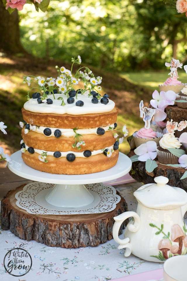 Fairy tea party cake! A layered vanilla cake with vanilla cream cheese buttercream, adorned with blueberries and fresh flowers
