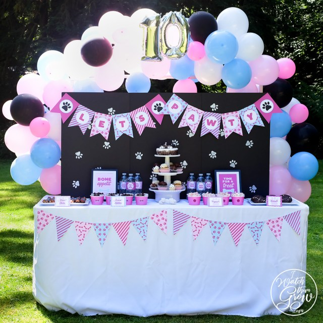 Puppy party treats table fully decorated with balloon arch, printable banner and bunting, and faux chalkboard table backdrop.