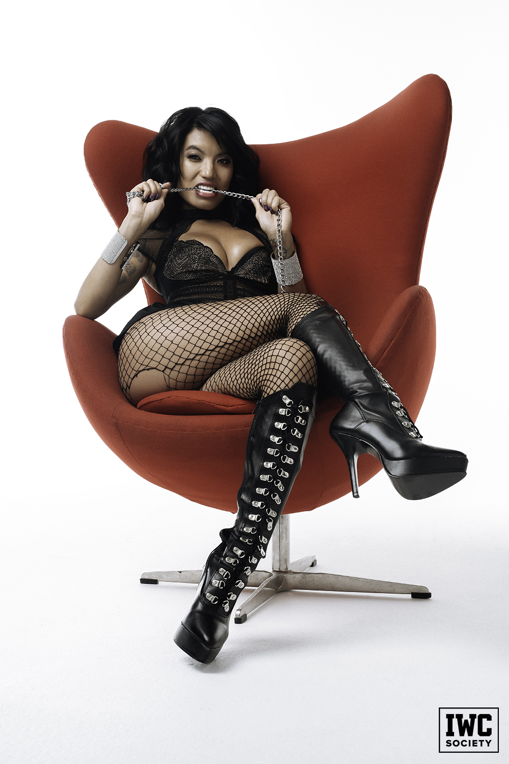 asian domme Asia Perez sitting cross-legged in black fishnets biting the chain of her male slave's collar