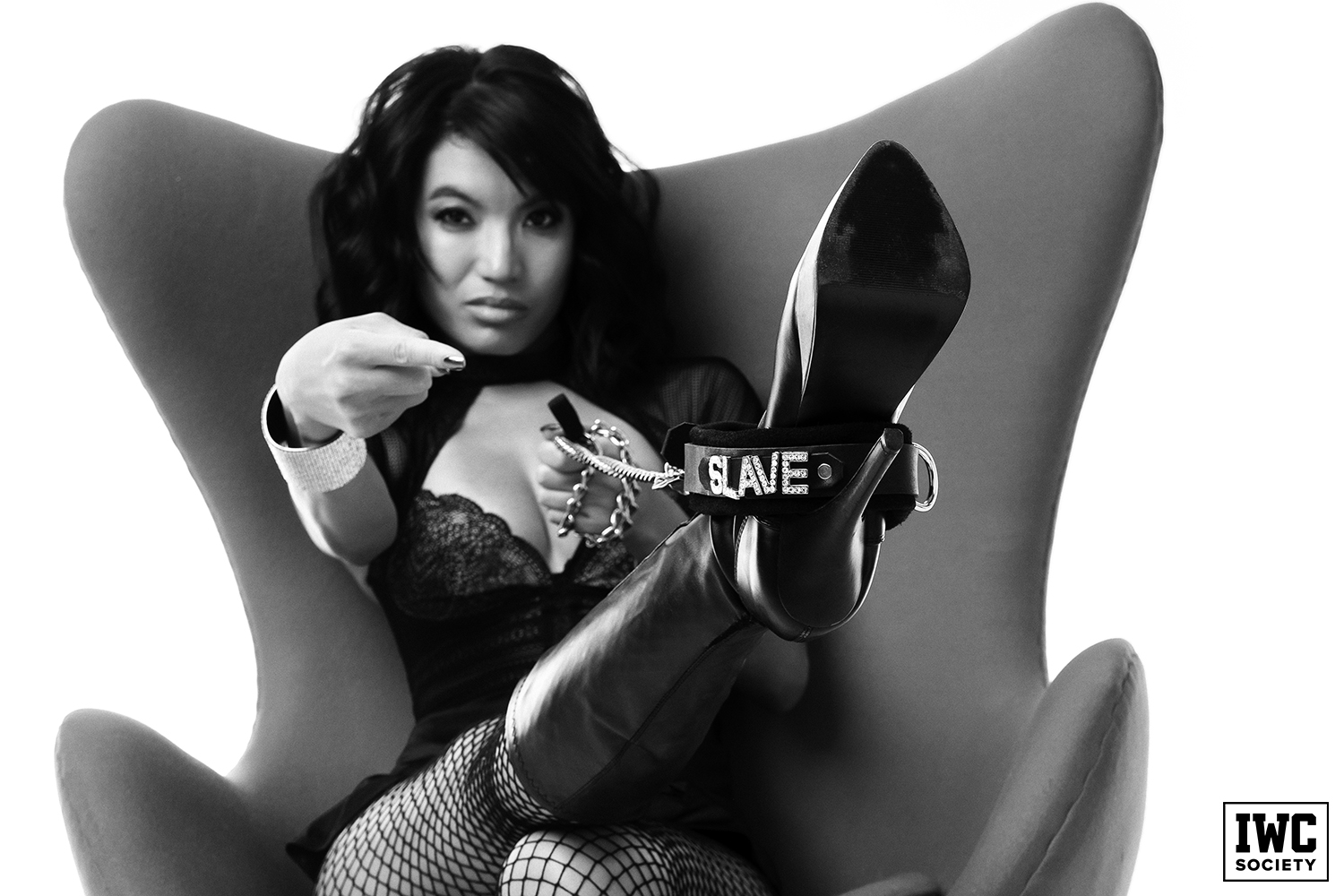 "asian dominatrix Asia Perez pointing to her boot which has a black color that says ""slave"" in rhinestones wrapper around it"