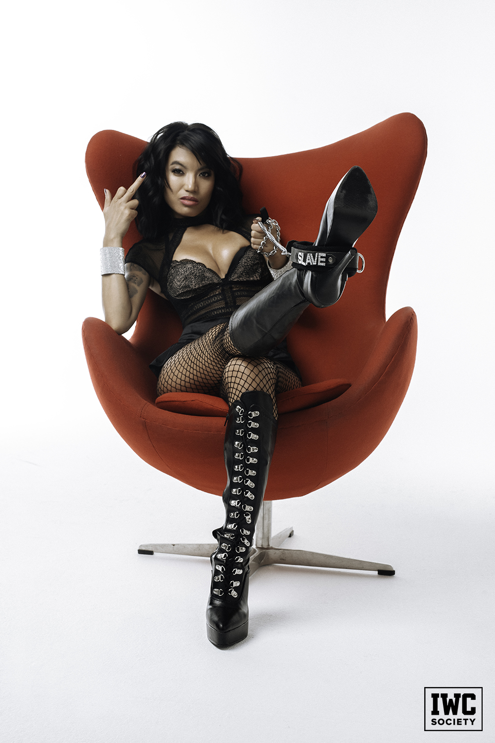 Goddess Asia Perez asian domme wearing black lingerie sitting in a red chair giving the middle finger
