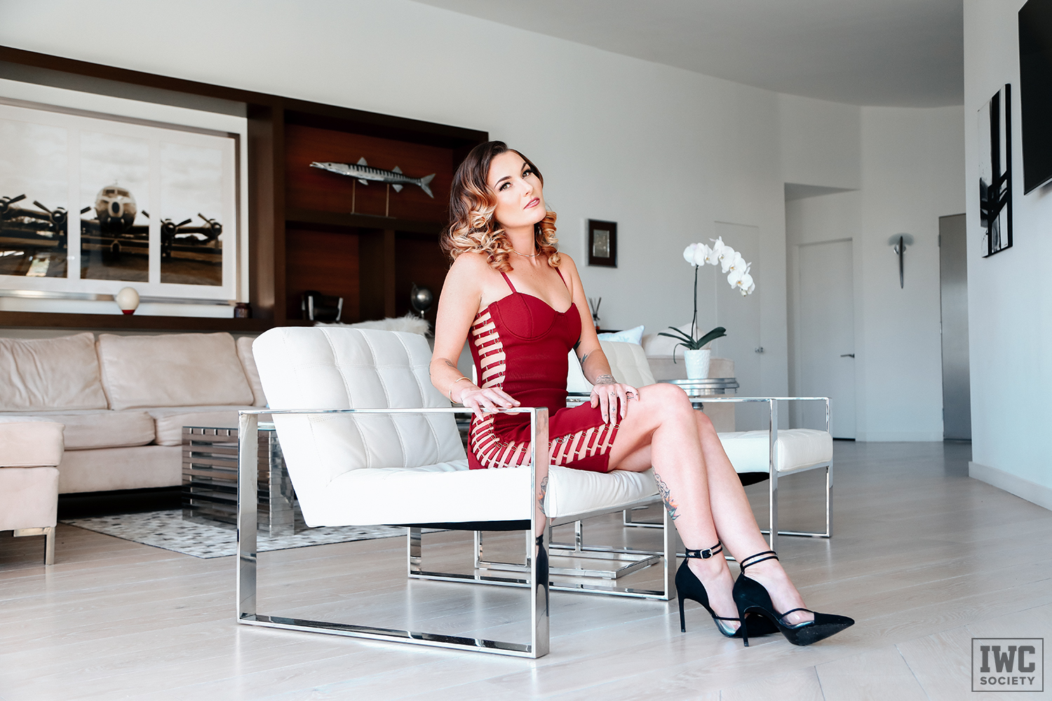 Goddess Emerald sexy findomme sitting on a modern white chair wearing a glamorous red dress