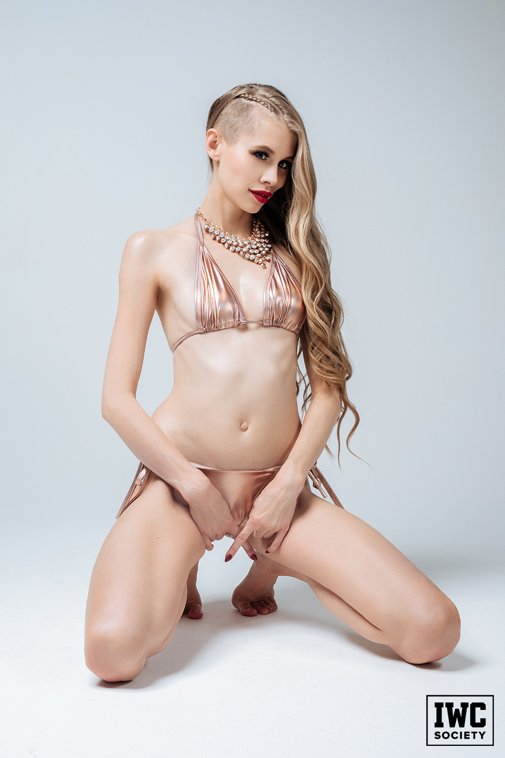 blonde domme goddess Kyaa in a gold bikini expressing tease and denial