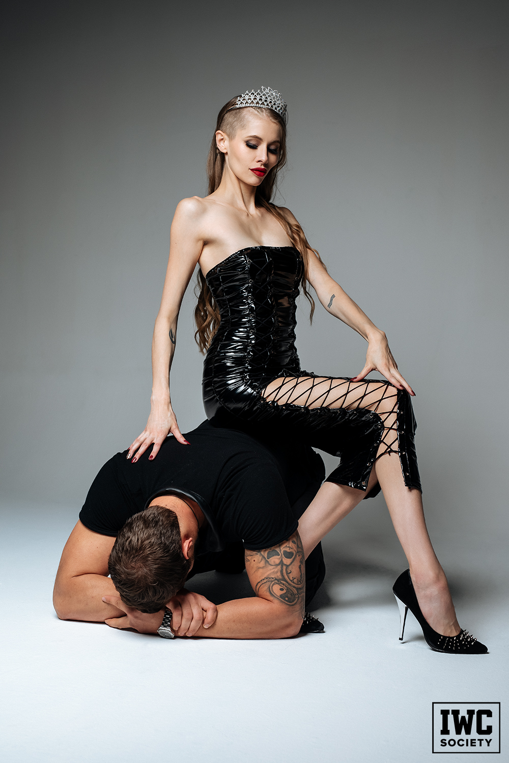 tall financial dominatrix Goddess Kyaa wearing a crown and sitting on her slave as human furniture