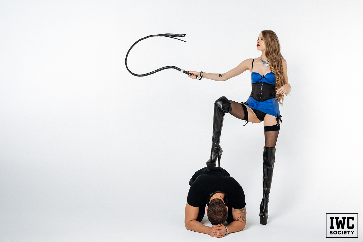 domme with long blonde hair in thigh high boots standing on a slave with a whip