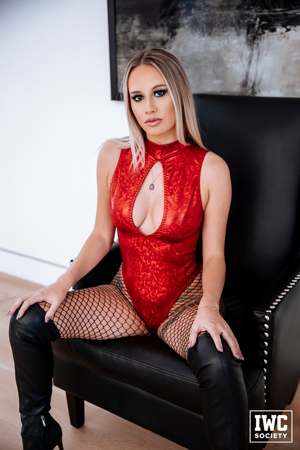 powerful greedy financial domme Goddess Lindsey wearing fishnets and a revealing shiny fetish red bodysuit