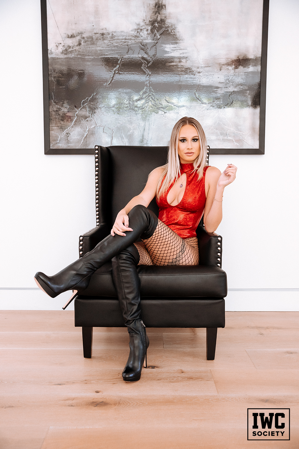 beautiful financial domination expert goddess lindsey wearing fishnets and boots sitting in black chair with legs crossed